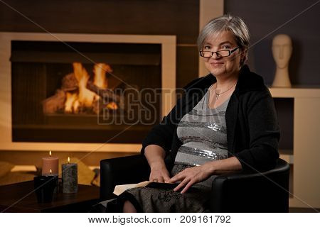 Mature woman sitting at fireplace on a winter day. reading book, smiling.