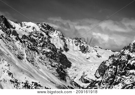 Black and white mountains with glacier in snow at winter sun day. View from ski lift on Hatsvali Svaneti region of Georgia. Caucasus Mountains.