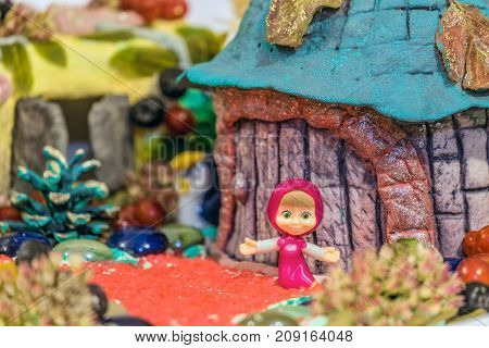 Belgorod Russia - September 19 2017: Figurine of character Masha from popular cartoon about Masha and the Bear in hand-made crafts scenery. Limited depth of field.