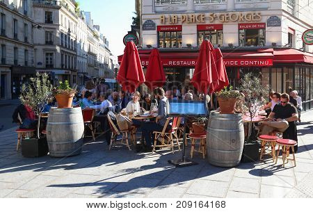 PARIS FRANCE -OCTOBER 14, 2017: A traditional restaurant A La Place St Georges in Paris in St.Georges Square. Parisians and tourists enjoy food and drinks on the terrace in the summer day.