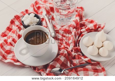 Coffee brake at restaurant. Porcelain cup of black coffee, lump sugar and smartphone with earphones on checkered tablecloth at white wooden background, copy space