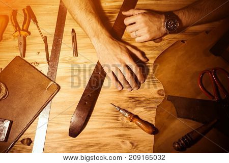 Working process of the leather belt in the leather workshop. Man holding hands on wooden table. Crafting tools on background. Tanner in old tannery. Close up men arm. Warm Light for text and design.