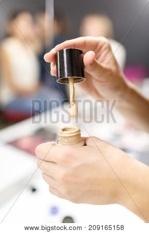 A woman make-up, holding a foundation in her hand. Beauty Studio. Close-up.