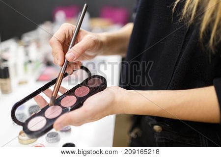 The hands of the make-up artist hold a brush and eye shadow. Showing the right tone. Close-up.