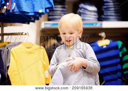 Cute Little Boy Choosing New Clothes During Shopping
