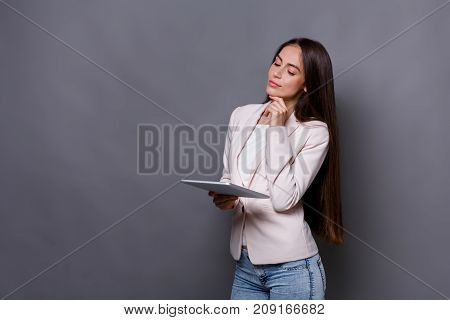 Technology. Business woman with digital device. Beautiful businesswoman at gray studio background with tablet, copy space