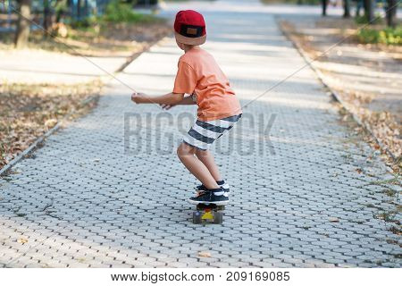Little Urban Boy With A Penny Skateboard. Kid Skating In A Summer Park. City Style. Urban Kids.