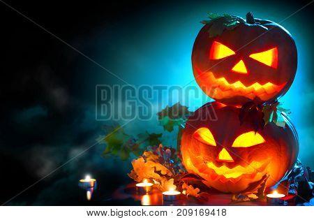 Halloween pumpkin head jack lantern with burning candles over black background. Halloween holidays border art design, celebration. Carved Halloween Pumpkins with burning candles