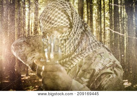 Portrait of face covered soldier aiming with rifle against trees in a woods