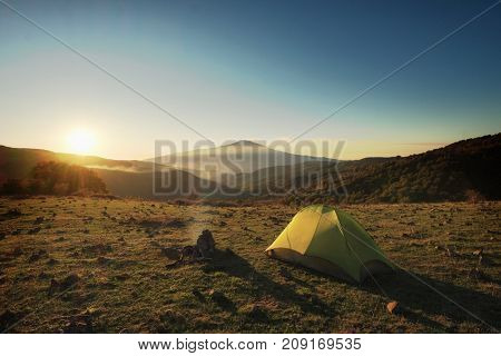 adventure scene tent pitched in Nebrodi Park, on background Etna Volcano - Sicily