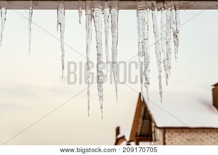 Icicles on the edge of roof overhang. Winter thaw.
