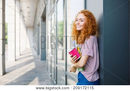 Happy redhead woman having a break between classes. Smiling girl outdoors at university campus. Education and entering the university concept. Copy space on the wall.