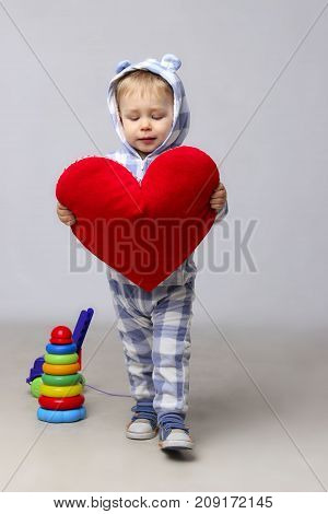 Kid With Red Heart. Little boy with red heart. Valentine's Day. Cute Little Boy With A Red Heart In The Hands.Charming Baby Holding A Red Heart In Hands.
