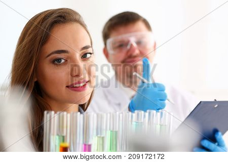 Smiling beautiful technician woman portrait and sample bottle with poison fluid. Medical worker in uniform use reagent tube for virus infection exam or biological toxic reaction, drug creation