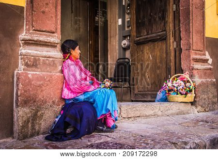 SAN MIGUEL DE ALLENDE GUANAJUATO / MEXICO - 06 27 2017: Mexican indigenous woman with traditional dress selling dolls