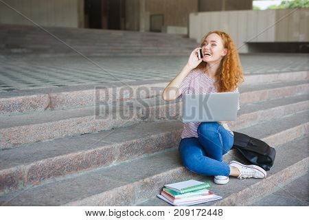 Happy redhead girl working with laptop, talking on the phone, sitting on the stairs outdoors. Young smiling woman having pleasant conversation. Communication and education concept