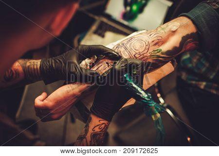 Tattoo artist makes a tattoo on a man's hand.