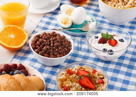 Rich continental breakfast menu. French crusty croissants, muesli, glass of orange fresh, yogurt and boiled eggs for tasty morning meals on checkered tablecloth