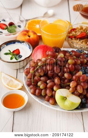 Fresh healthy breakfast with fruits closeup. Bowl with grapes, berries and apple with muesli, yogurt and orange juice on wooden table