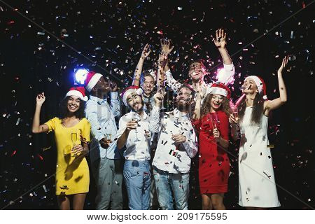 Party people. Group of young joyful friends having fun at birthday party at night club, showered with confetti, drinking champagne. Enjoying life and celebration concept