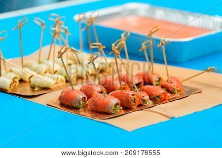 salmon rolls with spinach and bamboo skewers on a blue background