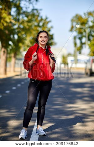 Young, beautiful girl in red uniform on a warm-up in the park with a rope