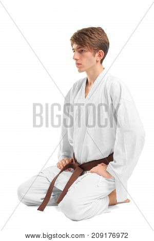Young guy karatek with brown belt on white isolated background sits on his knees