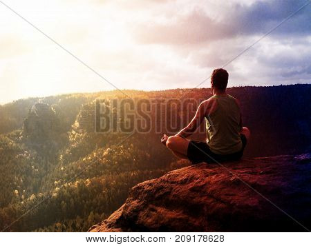 Man Meditating In Lotus Pose On Rocky Cliff. Sportsman Practicing Yoga On Peak