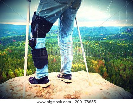 Lens defect. Man tourist wearing a knee brace with adjustable side panels to immobilize and support hurt leg. Man walking againts the crutches outdoors on hike trip poster