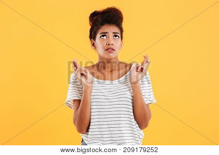 Young african nervous lady looking up and praying holding fingers crossed isolated over yellow