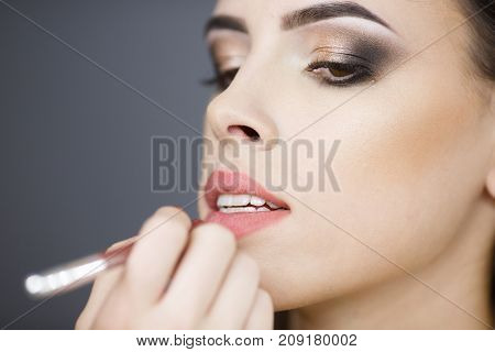 Beautiful young girl make-up artist paints lips. Close-up. In a studio. Concepts of style, beauty.