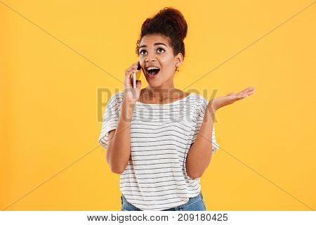 Happy african young woman in casual with open mouth talking on phone and looking isolated