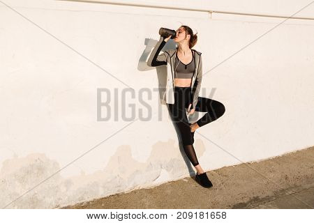 Full-length photo of young beautiful woman in sport wear drinking water, standing near white wall