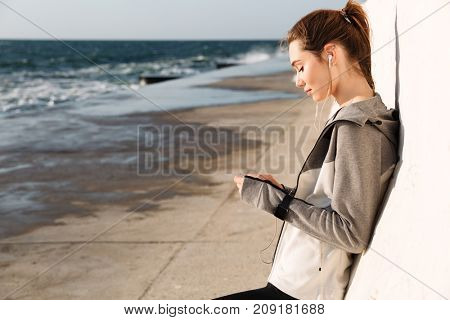 Close-up photo of young beautiful brunette woman in sport wear listening to music at the seaside