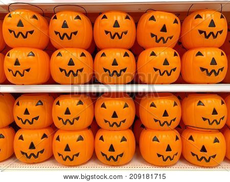 Orange plastic halloween pumpkin jack o lantern trick or treat buckets stacked and in rows on a department store shelf ready for shoppers this holiday season.