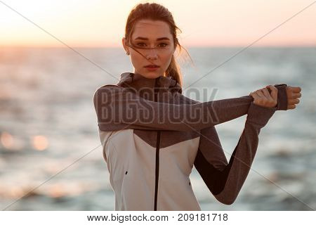 Close-up photo of beautiful brunette woman doing stretching exercise at the beach, looking at camera