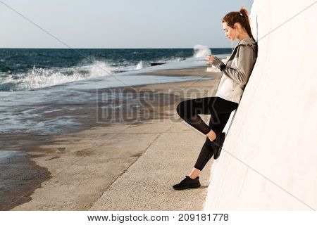 Full-length photo of young slim sport woman, using mobile phone, standing near white wall, seaside outdoor