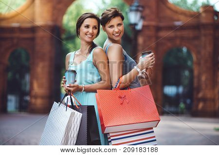 Two young sisters or friends walking in a shopping center with shopping paper bags. Women having smiling and having fun. Brick, vintage, industrial background.
