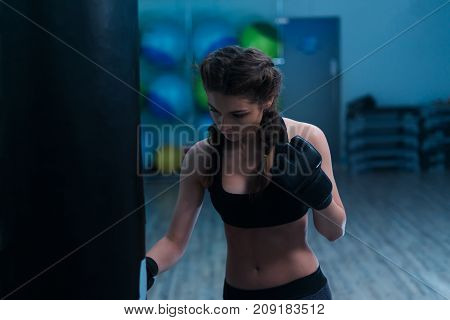 Young fighter boxer fit girl wearing boxing gloves in training. She is beating heavy punching bag in gym.  Woman power concept