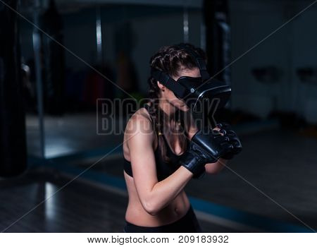 Young fighter boxer fit girl in VR glasses wearing boxing gloves in training defending from unseen enemy. Boxing game in virtual reality 360 degrees. Futuristic gaming