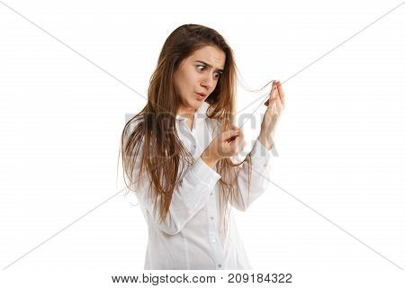 Sad young girl posing on the camera in studio and touching hair isolated on a white background. Beautiful girl in white shirt. Close-up of woman.