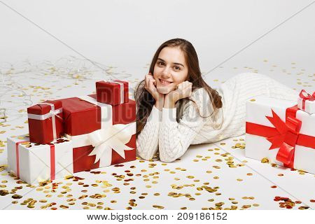 Young girl with gifts isolated on white background. Lies on the floor with confetti and gifts. The concept of a holiday. Close-up.