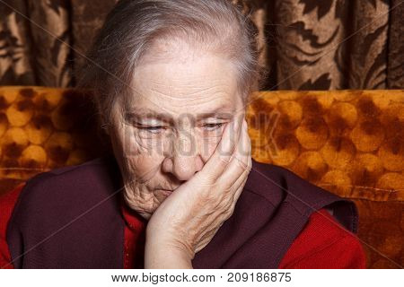 senior woman sitting in sofa and thinking