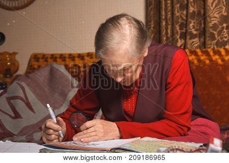An old woman solves crossword puzzles on table
