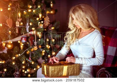Winter Holidays, Celebration And New Year Concept - Woman Unboxing Present Under Christmas Tree With
