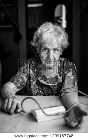 Black and white portrait of an elderly woman with a machine measuring blood pressure.