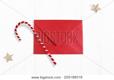 Christmas mockup scene with red envelope, candy cane decoration and stars made of birch bark on white wooden background. Empty space for your text. Top view.