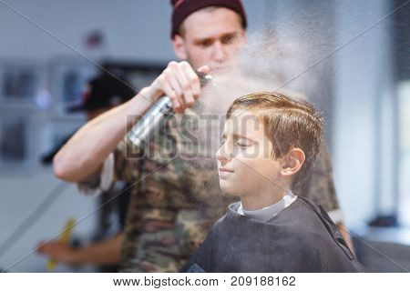 Hairdresser short-cropped in a brown hat in a barbershop makes a haircut for a young guy pushes water on her hair