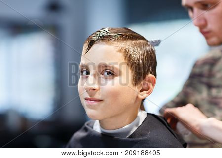 Hairdresser short-cropped in a brown hat in a barbershop makes a haircut for a young guy. Handsome hairdresser does a haircut for a little boy