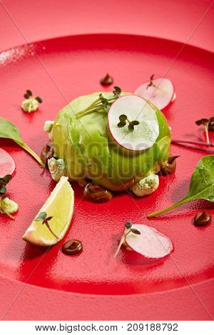 Pan-Asian menu in restaurant - dish called Kamchatka ball - crab inside outside avocado with fruit and vegetable slices sprinkled with fresh herbs on red plate